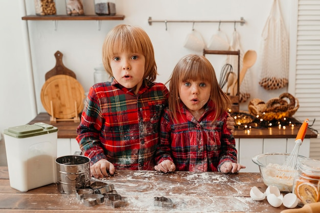Verrast kinderen samen kerstkoekjes maken