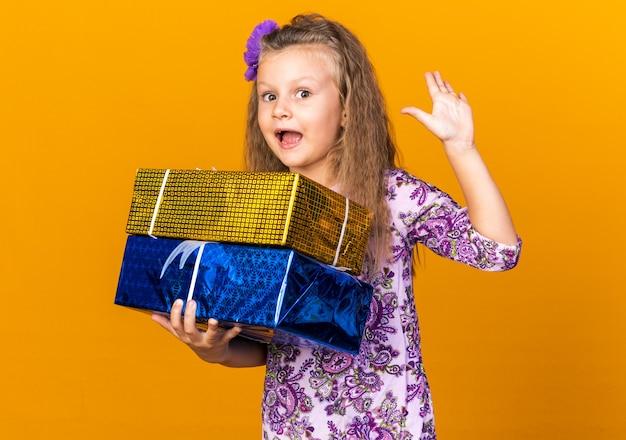 Verrast klein blond meisje dat geschenkdozen vasthoudt en hand opsteekt geïsoleerd op een oranje muur met kopieerruimte