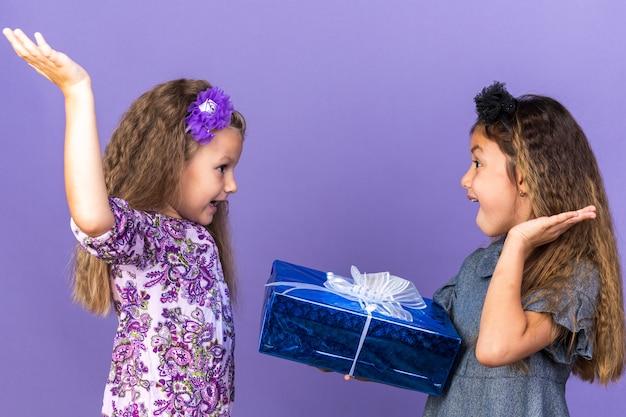 Verrast klein blond meisje dat met opgeheven handen staat en naar haar vriend kijkt die een geschenkdoos vasthoudt op een paarse muur met kopieerruimte