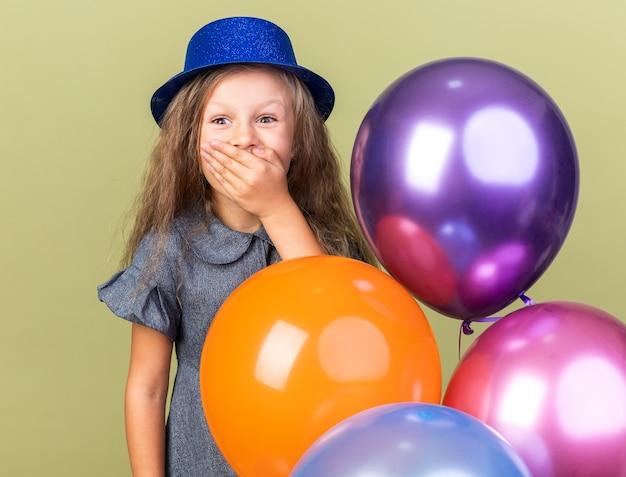 Verrast klein blond meisje met blauwe feestmuts die hand op mond zet en heliumballonnen vasthoudt geïsoleerd op olijfgroene muur met kopieerruimte