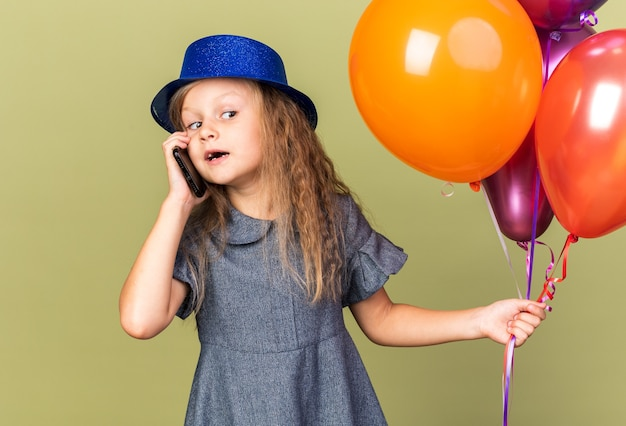 Verrast klein blond meisje met blauwe feestmuts met heliumballonnen en pratend over de telefoon, kijkend naar kant geïsoleerd op olijfgroene muur met kopieerruimte