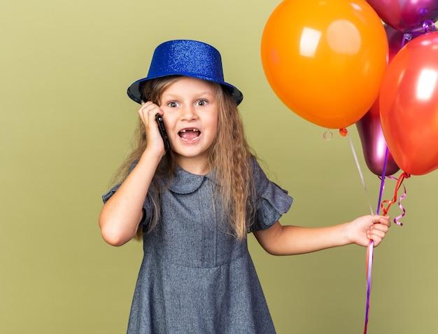 Verrast klein blond meisje met blauwe feestmuts met heliumballonnen en pratend over telefoon geïsoleerd op olijfgroene muur met kopieerruimte