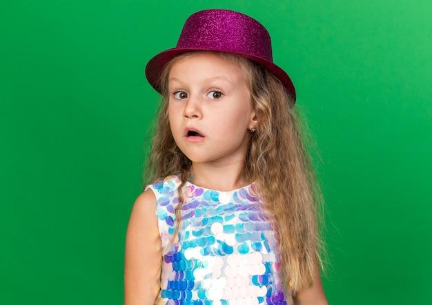 Verrast klein blond meisje met paarse feestmuts op zoek geïsoleerd op groene muur met kopieerruimte