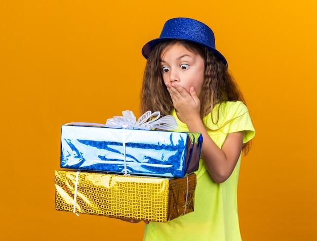 Verrast klein kaukasisch meisje met blauwe feestmuts die de hand op de mond legt en geschenkdozen vasthoudt die op een oranje muur met kopieerruimte zijn geïsoleerd