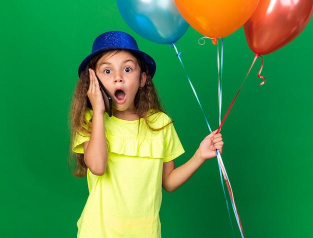 Verrast klein kaukasisch meisje met blauwe feestmuts helium ballonnen te houden en te praten over de telefoon geïsoleerd op groene muur met kopie ruimte