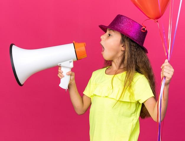 Verrast klein kaukasisch meisje met paarse feestmuts die heliumballonnen vasthoudt en in een luidspreker spreekt die naar de zijkant kijkt geïsoleerd op roze muur met kopieerruimte