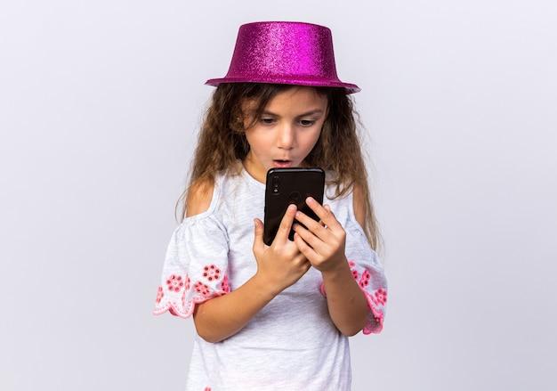 Verrast klein kaukasisch meisje met paarse feestmuts die telefoon vasthoudt en kijkt op een witte muur met kopieerruimte