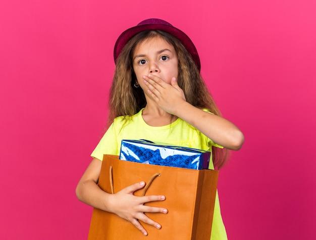Verrast klein kaukasisch meisje met paarse feestmuts hand op de mond te zetten en geschenkdoos te houden in een papieren zak geïsoleerd op roze muur met kopie ruimte