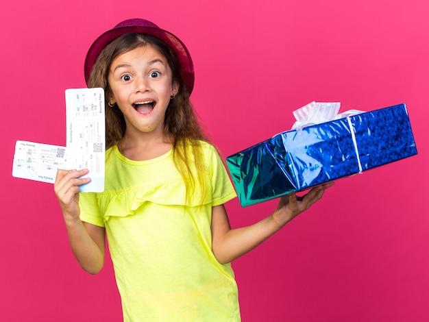 Verrast klein kaukasisch meisje met paarse feestmuts met geschenkdoos en vliegtickets geïsoleerd op roze muur met kopie ruimte