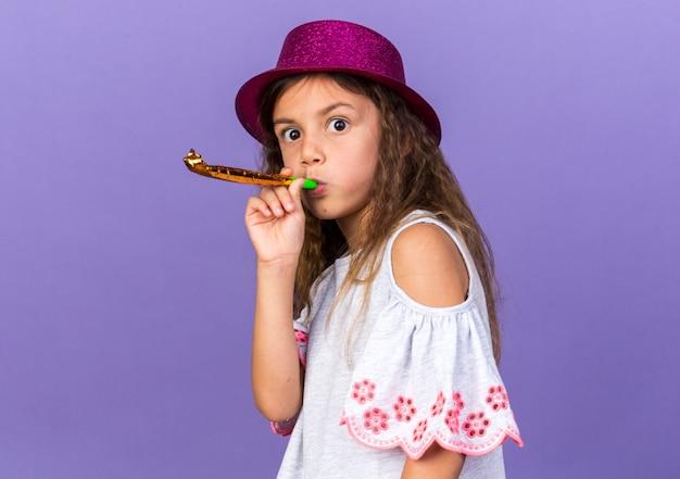 Verrast klein kaukasisch meisje met violette feestmuts waait partij fluitje geïsoleerd op paarse muur met kopie ruimte