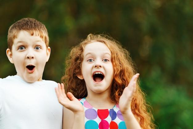 Verrast klein meisje en jongen op lente buitenshuis.