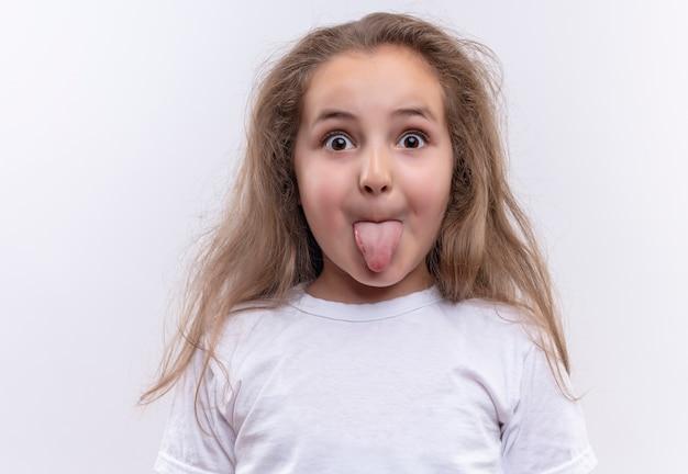 Verrast klein schoolmeisje dat witte t-shirt draagt die tong op geïsoleerde witte achtergrond toont
