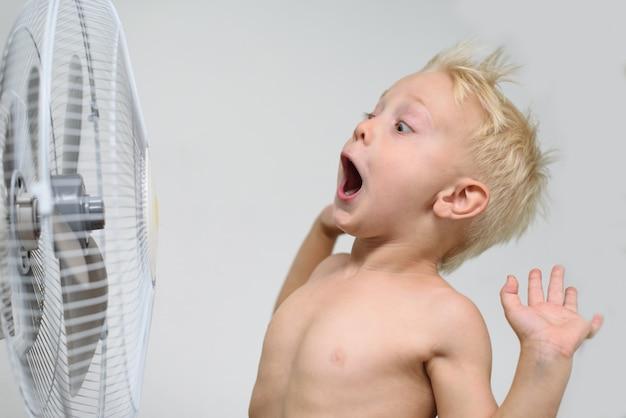 Verrast kleine blonde jongen met open mond en naakte torso staat in de buurt van een ventilator. zomer concept