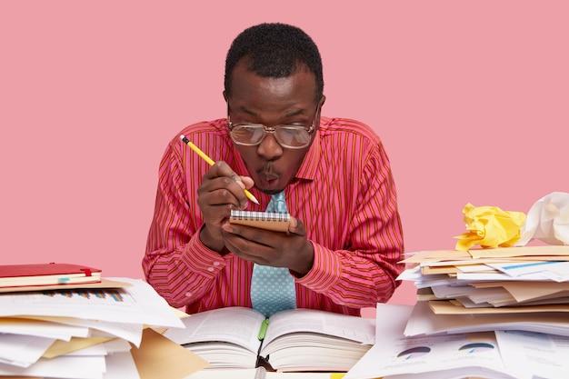 Verrast knappe afro-amerikaanse mannelijke financier schrijft planningstips in spiraal kladblok met potlood, kijkt geschokt en heeft veel dingen te doen