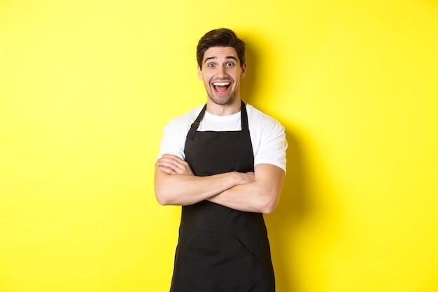 Verrast knappe barista in zwarte schort die wenkbrauwen opheft, verbaasd kijkt, staande tegen een gele achtergrond