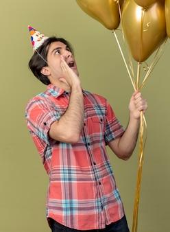 Verrast knappe blanke man met verjaardagspet houdt hand dicht bij mond kijkend naar heliumballonnen