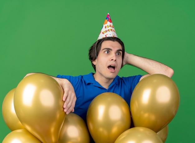 Verrast knappe blanke man met verjaardagspet legt hand op het hoofd achter staan met heliumballonnen