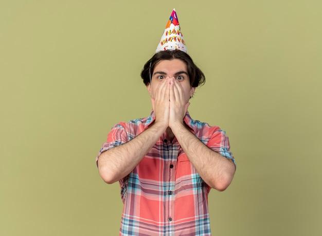 Verrast knappe blanke man met verjaardagspet legt handen op mond kijkend naar camera