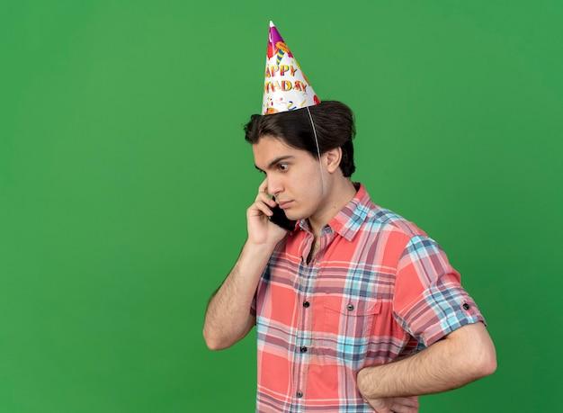 Verrast knappe blanke man met verjaardagspet staat zijwaarts pratend aan de telefoon