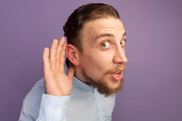 Verrast knappe blonde man houdt hand achter oor geïsoleerd op paarse muur