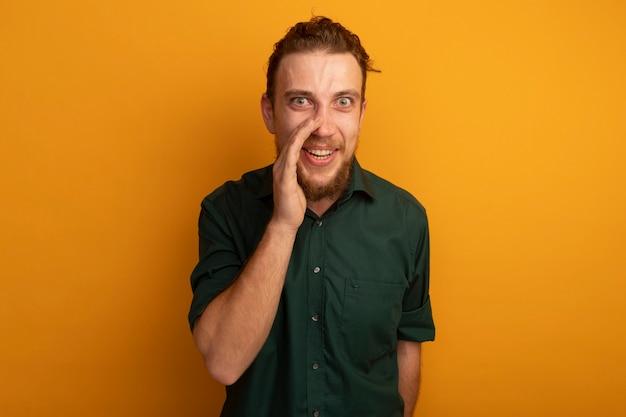 Verrast knappe blonde man houdt hand dicht bij mond op oranje