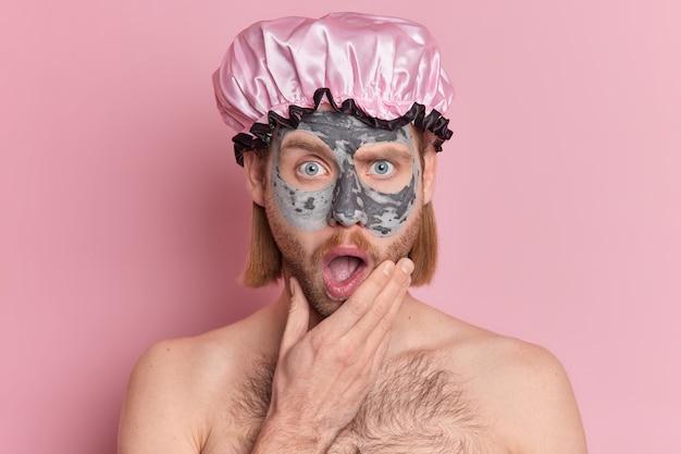Verrast knappe kerel past schoonheid gezichtsmasker houdt mond open draagt badmuts heeft naakt lichaam.