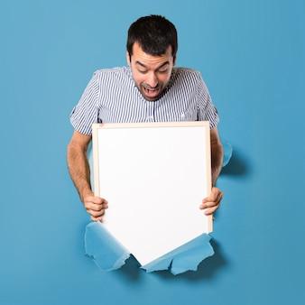 Verrast knappe man die een leeg bordje door een papier gat