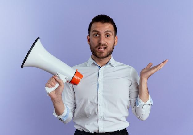 Verrast knappe man houdt luidspreker geïsoleerd op paarse muur
