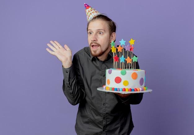 Verrast knappe man in verjaardag glb houdt cake steekt hand op kijken naar kant geïsoleerd op paarse muur
