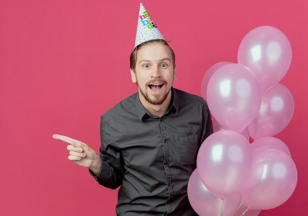 Verrast knappe man in verjaardag glb staat met helium ballonnen wijzend naar de zijkant