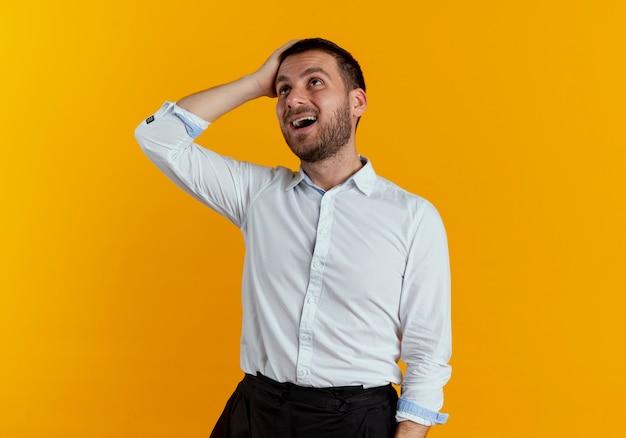 Verrast knappe man legt hand op voorhoofd opzoeken geïsoleerd op oranje muur