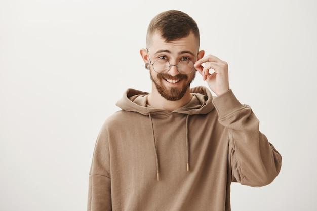 Verrast knappe man opstijgen bril en geïntrigeerd kijken