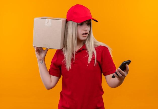 Verrast levering jong meisje met rode t-shirt en pet met doos op schouder kijken naar telefoon op haar hand op geïsoleerde oranje achtergrond