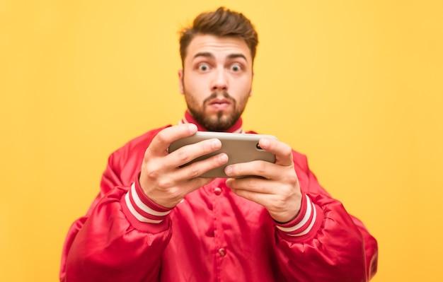 Verrast man draagt een rode jas, houdt een smartphone in zijn handen, geïsoleerd op geel