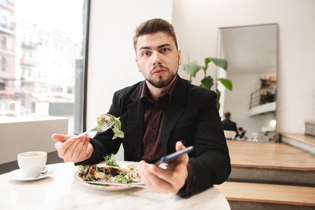 Verrast man in een pak zit in een gezellig restaurant met een smartphone in zijn handen, eet een salade met een bord met een vork en kijkt naar de camera.