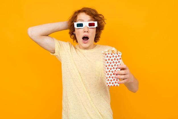 Verrast man in een t-shirt met popcorn kijken naar een film met 3d-bril op een gele achtergrond met kopie ruimte