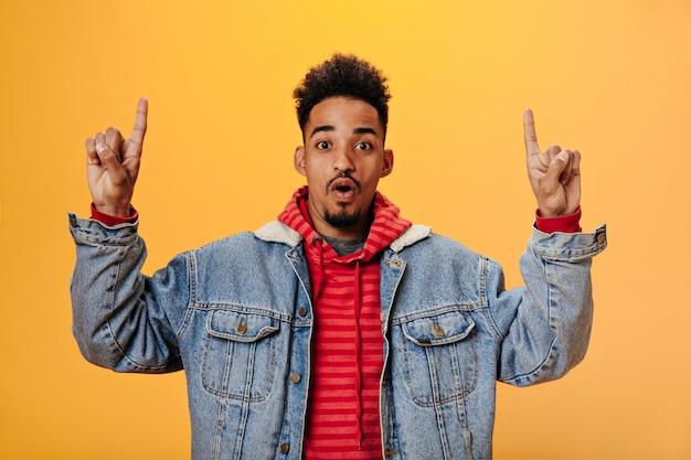Verrast man in spijkerjasje toont vingers op plaats voor tekst op oranje muur