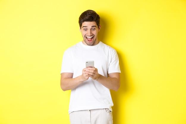 Verrast man leest sms-bericht op mobiele telefoon, kijkt verbaasd en blij op het scherm van de smartphone, staande op een gele achtergrond