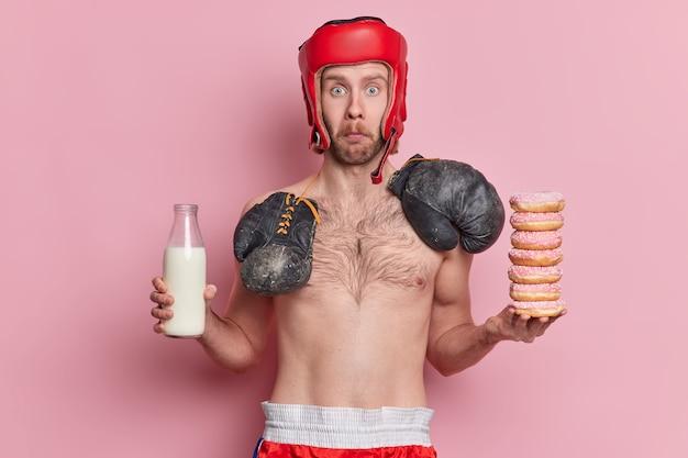 Verrast man met blauwe ogen staart draagt beschermende hoed bokshandschoenen om nek heeft naakte torso houdt fles melk vast en stapel donuts heeft verleiding om junkfood te eten