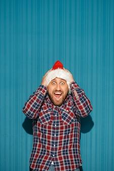 Verrast man met een kerstmuts op blauwe achtergrond