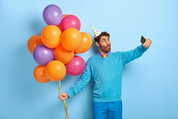 Verrast man met verjaardagshoed en ballonnen poseren in blauwe trui