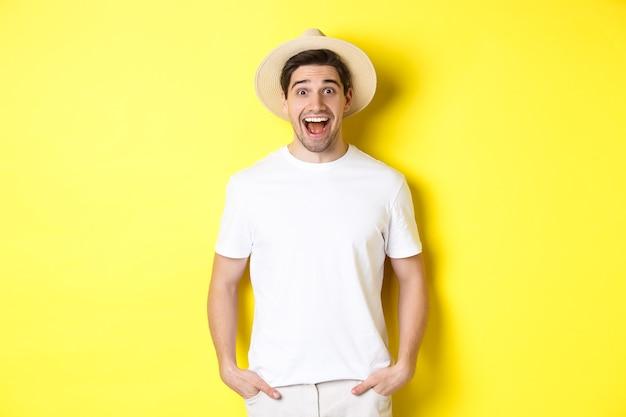 Verrast man toerist in strohoed die er gelukkig uitziet, verbaasd reageert op reclame van reisbureaus, staande over gele achtergrond