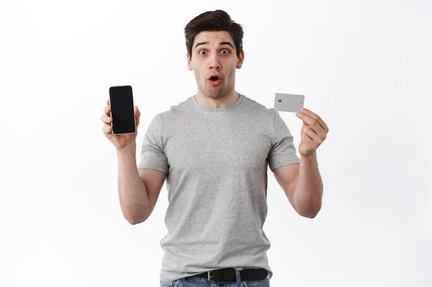 Verrast man toont leeg scherm van mobiele telefoon en plastic creditcard, hijgend en zegt wauw, onder de indruk van online winkel, bestelt, staat tegen witte muur