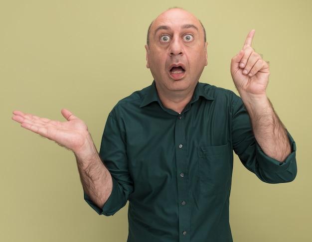 Verrast man van middelbare leeftijd met groene t-shirtpunten met hand aan zijpunten naar boven geïsoleerd op olijfgroene muur