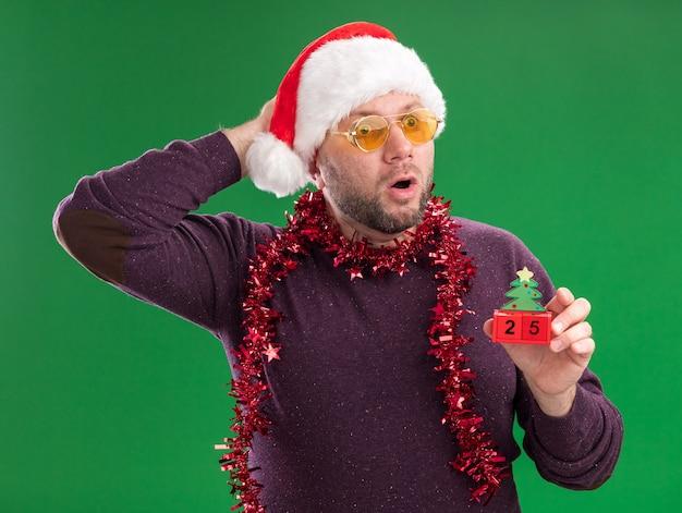 Verrast man van middelbare leeftijd met kerstmuts en klatergoud slinger rond nek met glazen kerstboom speelgoed te houden