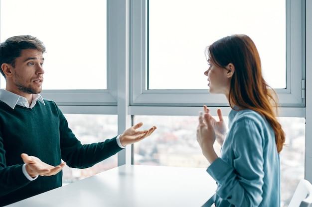 Verrast man zit aan een tafel en gebaren met zijn handen en een geïnteresseerde vrouw