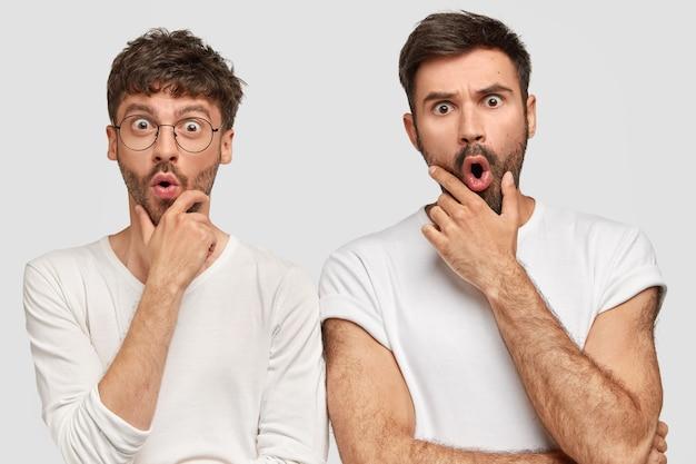 Verrast mannelijke bedrijfsmedewerkers hebben hun uitdrukkingen verbijsterd, houden hun kin vast en staren met afgeluisterde ogen