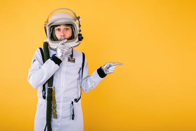 Verrast mannelijke kosmonaut in ruimtepak en helm, wijzende vinger naar rechts, op gele muur.