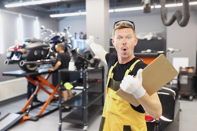 Verrast mannelijke reparateur met klembord met documenten en wijzende vinger naar motorfiets
