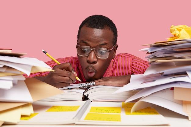 Verrast mannelijke student-ontwerper maakt schetsen in spiraalvormig notitieblok, draagt een grote bril, heeft een verbijsterde gezichtsuitdrukking, houdt potlood vast
